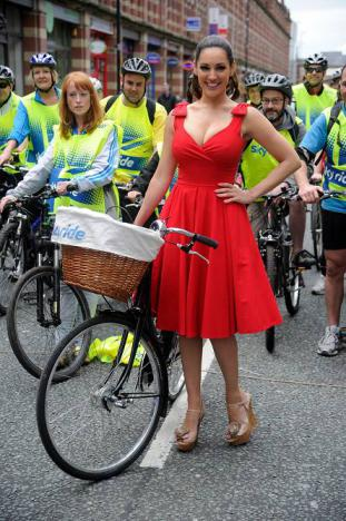 Kelly Brook poses with sky ride bike