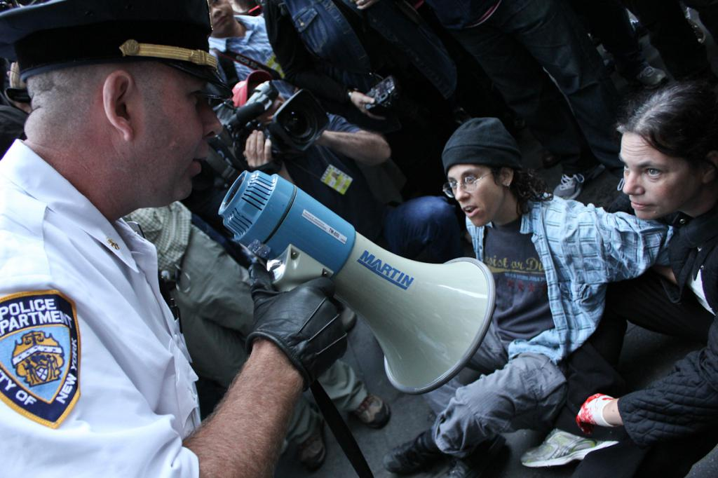 Cop with microphone speaks to protesters
