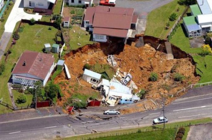 houses and cars in large Sinkhole