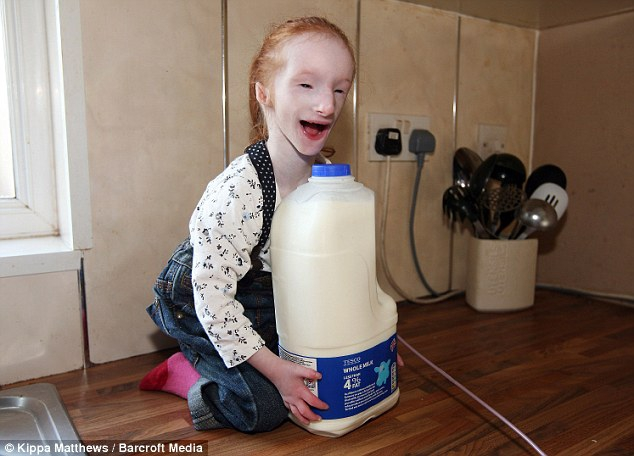 Worlds Smallest Girl Sitting next to gallon of milk