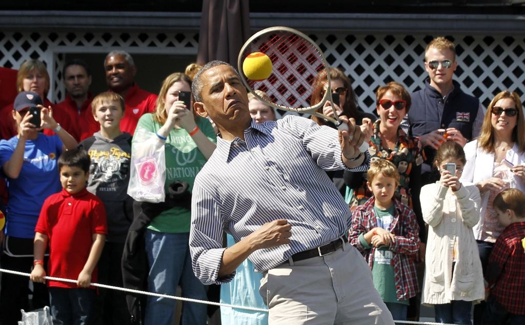 Barack Obama attempting to play tennis