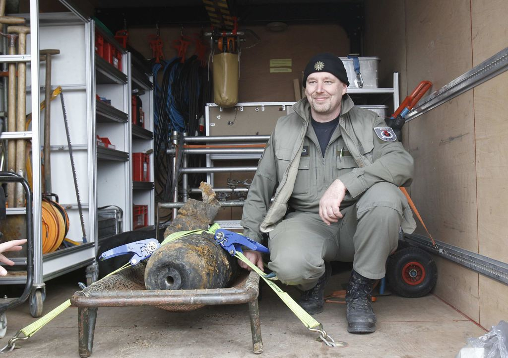 Joerg Neumann of the German bomb disposal team poses next to a diffused unexploded World War II bomb