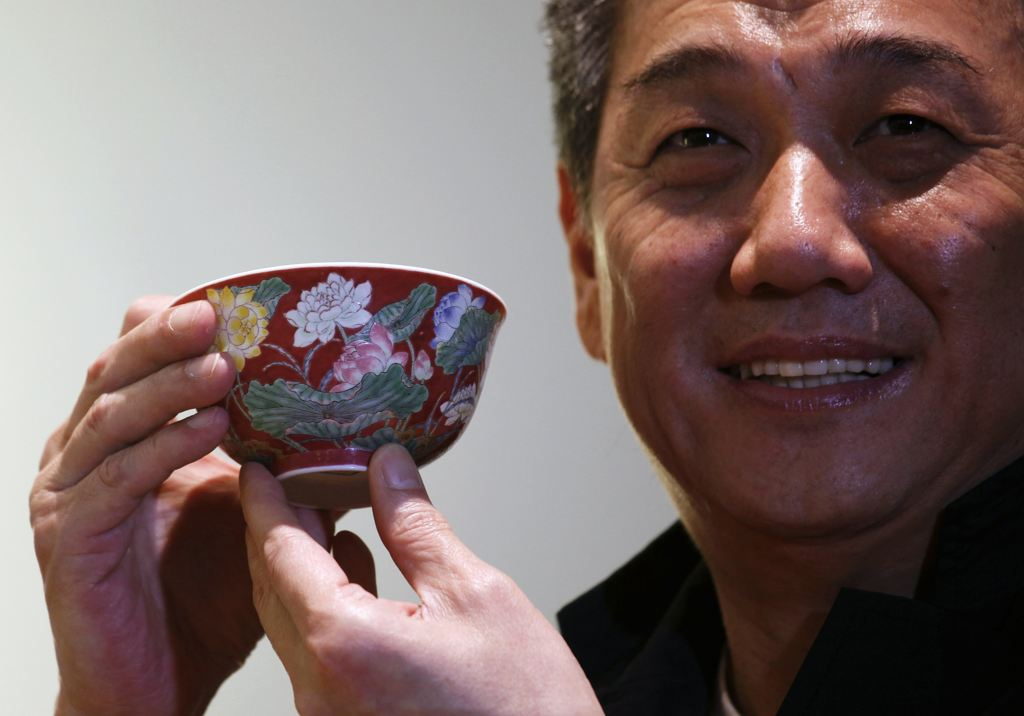 "Hong Kong Chinese ceramics dealer William Chak poses with a magnificent Ruby-Ground Falangcai ""Double-Lotus"" Bowl"