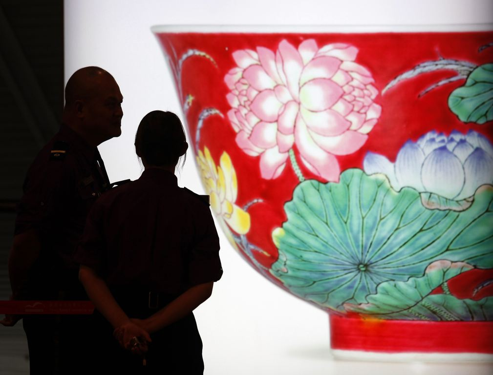 "Security guards chat in front of a light box featuring a photograph of a magnificent Ruby-Ground Falangcai ""Double-Lotus"