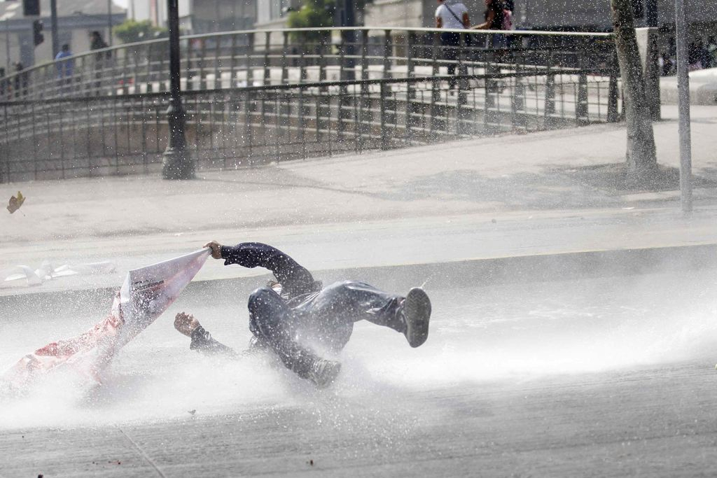 A student protester is hit by a jet of water released from a riot police water cannon