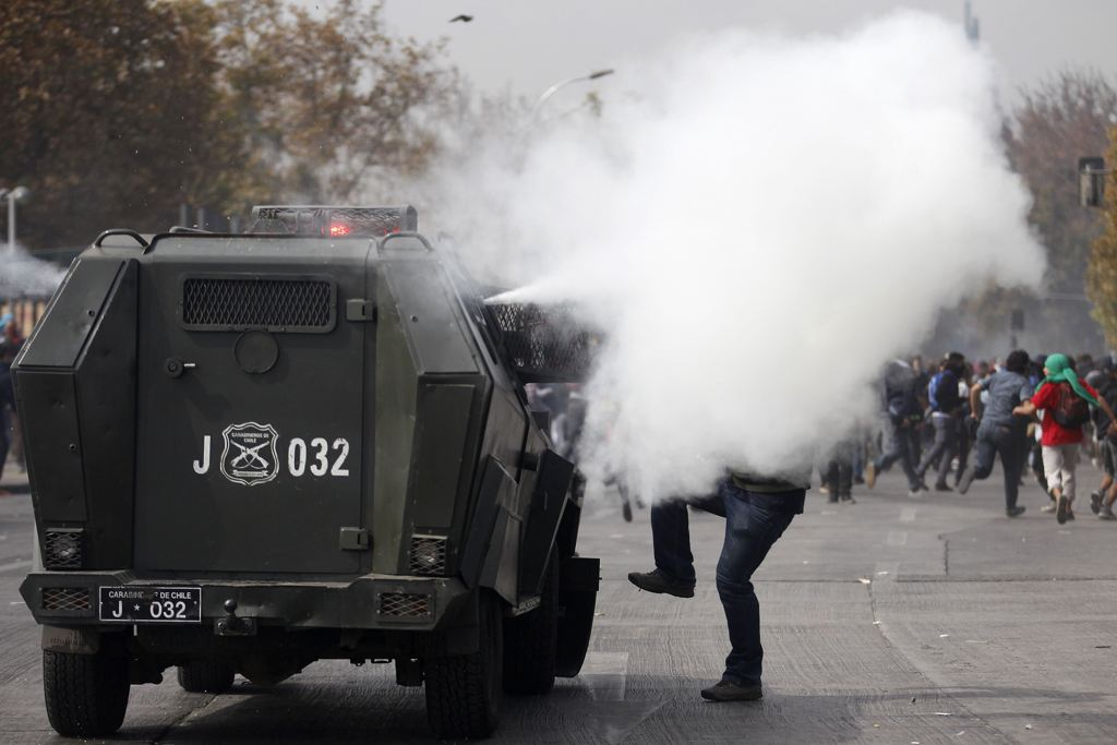 A student protester is covered by a tear gas cloud from a police vehicle