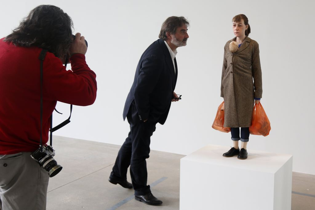 "A visitor looks at a sculpture entitled ""Woman with Shopping, 2013"" by artist Ron Mueck"