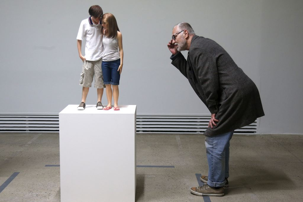 "A visitor looks at a sculpture entitled ""Young Couple, 2013"""