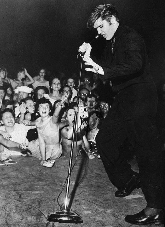 Borsi standing in the front row with her cell phone camera pointed at Presley