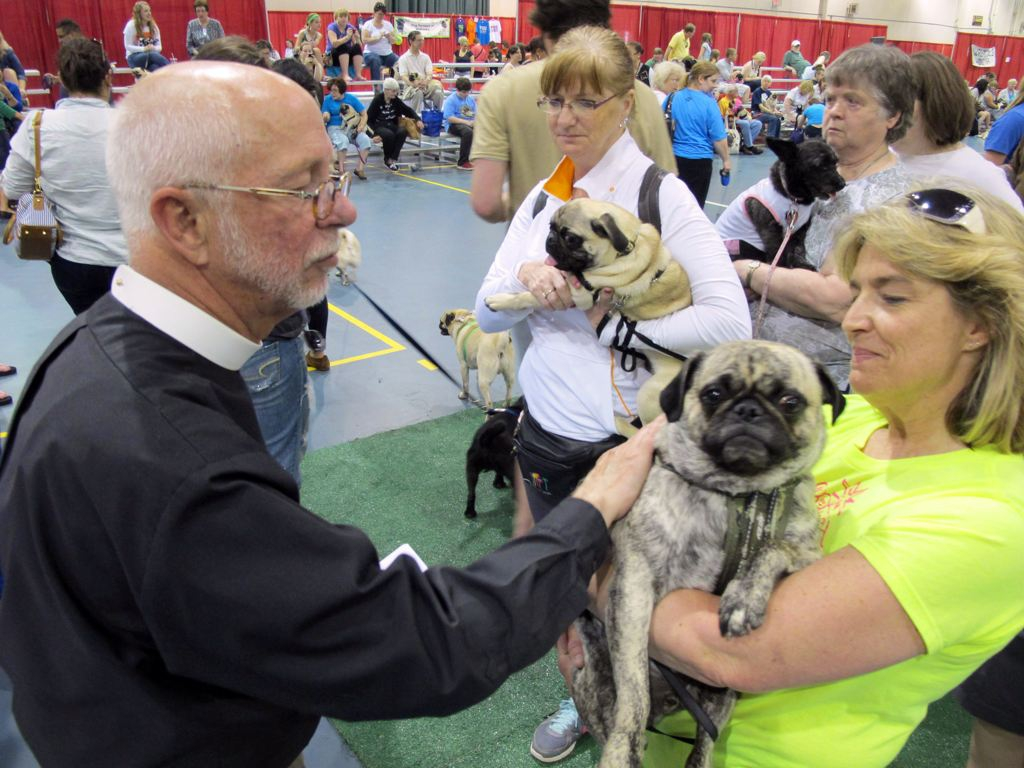 Father John Allen blesses Chip, who is being held by Lisa Erdmann