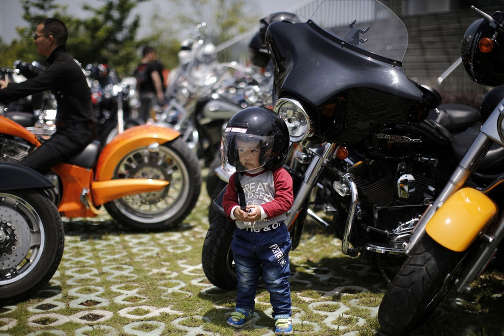 A local boy wearing a helmet poses next to a Harley Davidson motorcycle in Zhejiang Province, on May 11, 2013.