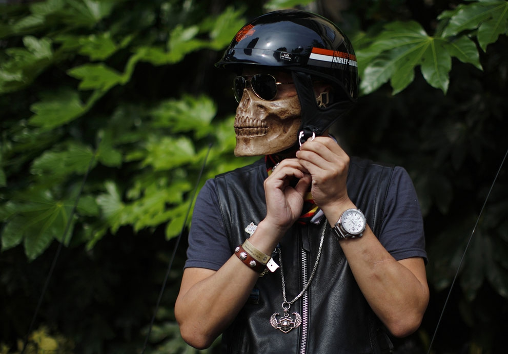 A man wearing a skeleton mask prepares to ride his Harley Davidson motorcycle during the annual Harley Davidson National