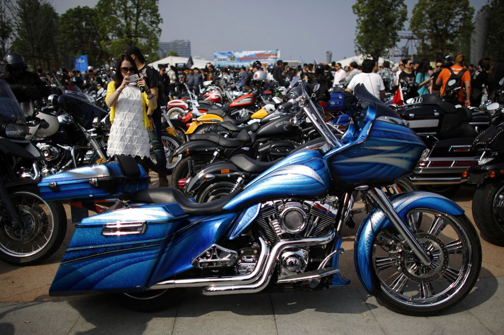 A woman takes a picture of a customized Harley Davidson during an annual rally in Qian Dao Lake, on May 11, 2013.