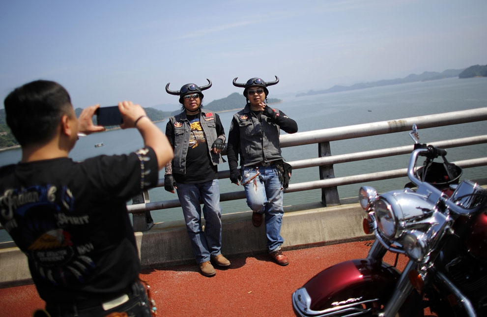 Helmeted riders pose in Qian Dao Lake, on May 11, 2013.