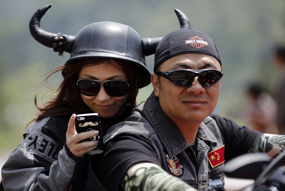 A couple rides a Harley Davidson motorcycle during the annual Harley Davidson National Rally in Qian Dao Lake, in Zhejia